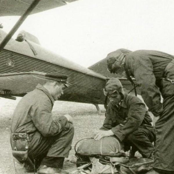 24.Летчик перед вылетом осматривает парашют.