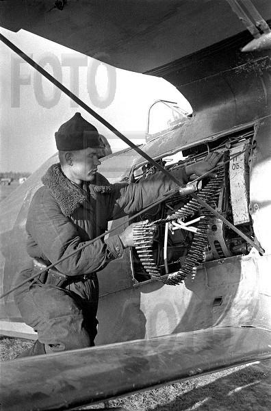 26а.Н-ская авиачасть. Комсомолец ефрейтор С.Форман заряжает пулемет на И-153.