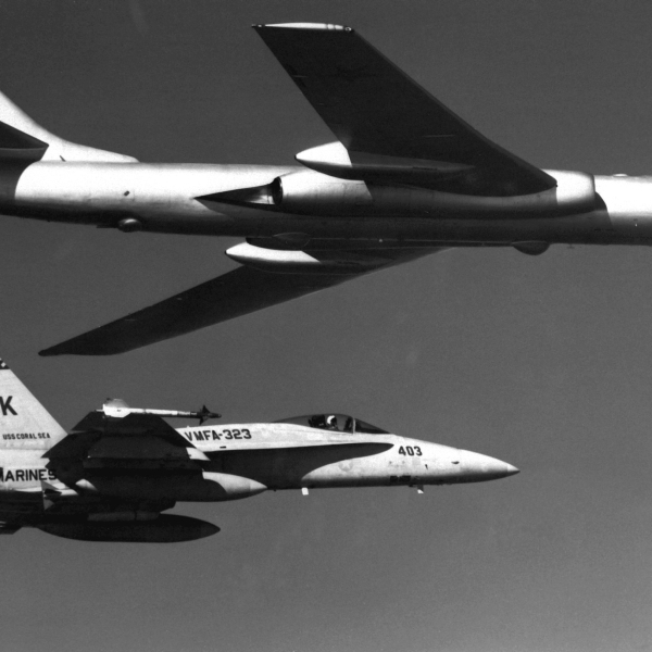 An air-to-air right side view of a Soviet TU-16 Badger aircraft being escorted by an F/A-18A Hornet aircraft from Marine Fighter Attack Squadron 323 (VFMA-323).