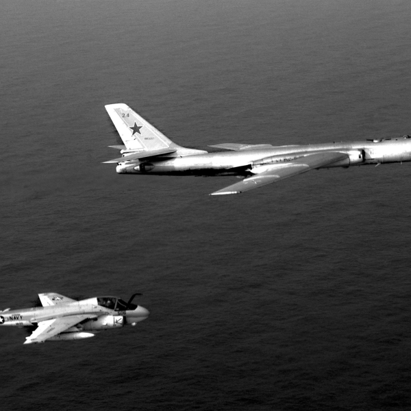 An air-to-air right side view of a Medium Attack Squadron 95 (VA-95) A-6E Intruder aircraft, assigned to the nuclear-powered aircraft carrier USS ENTERPRISE (CVN 65), escorting a Soviet Tu-16 Badger aircraft.