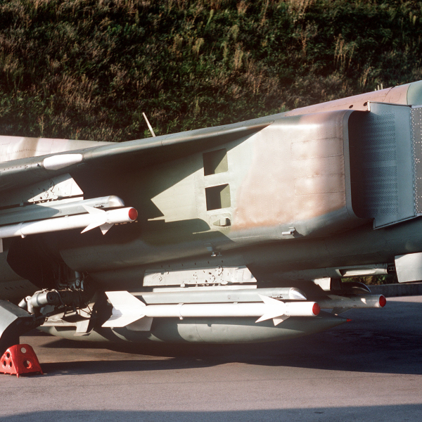 Close-in view of the right midsection of a Soviet MiG-23 Flogger B fighter aircraft showing AAM-2 Atoll missiles attached to the undercarriage and wing pylons. The aircraft is on public display at the Memorial Complex of the Ukrainian State.